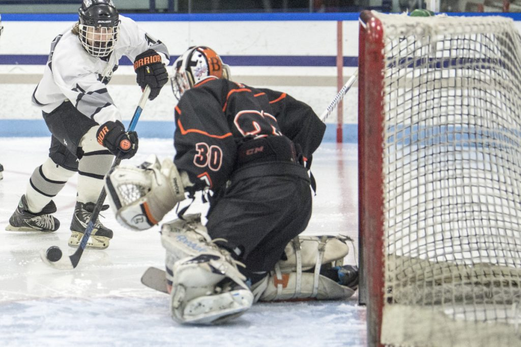 Kennebec's Tommy Tibbetts, left, puts a shot on Brewer goalie Tyler St. Lawrence in the second period last month at Colby College in Waterville.