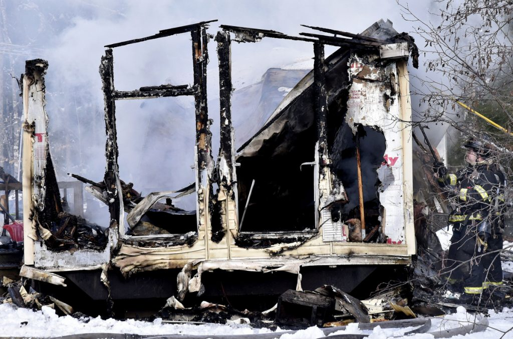 Firefighters pull burnt siding off a smoking mobile home on U.S. Route 2 in Norridgewock that was destroyed by fire on Wednesday.