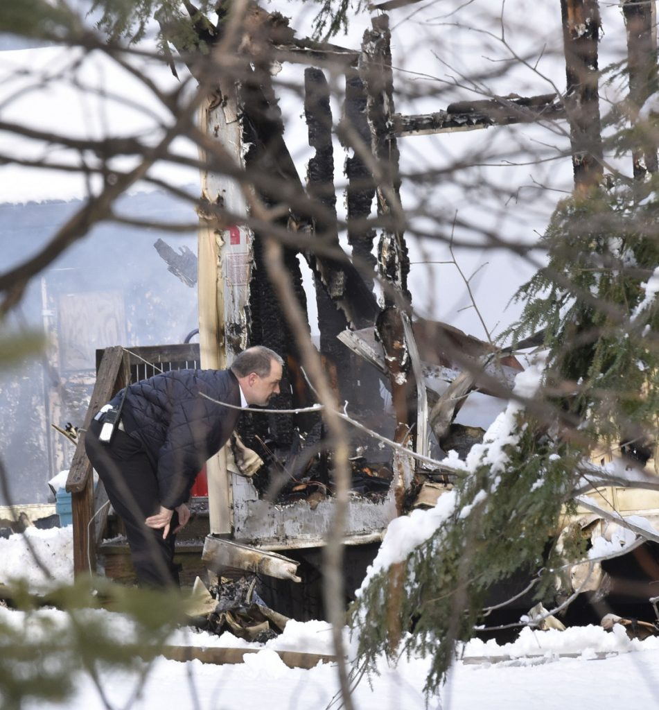 Skowhegan Fire Chief Shawn Howard inspects the scene of a fire as firefighters from Norridgewock and Skowhegan put out the fire that destroyed a mobile home on U.S. Route 2 in Norridgewock on Wednesday.