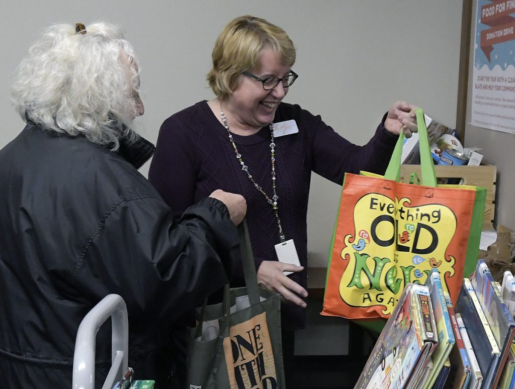 Pat Greve, left, hands Lithgow Public Library employee Kathy Petersen bags of toiletries and food at the front desk Wednesday in Augusta. The library is running a fine forgiveness program through the end of January permitting cardholders to donate nonperishable food and essential items in exchange for having their overdue fines forgiven. Greve, of Hallowell, donates her time at the library.