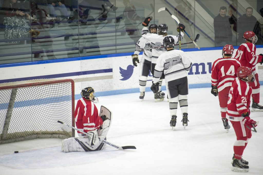 Kennebec's Hunter Brown, facing, celebrates a first-period goal with teammates Tommy Tibbetts and Brandon Bearce as Cony  goalie Matty Shea takes a knee Wednesday at Colby College in Waterville.
