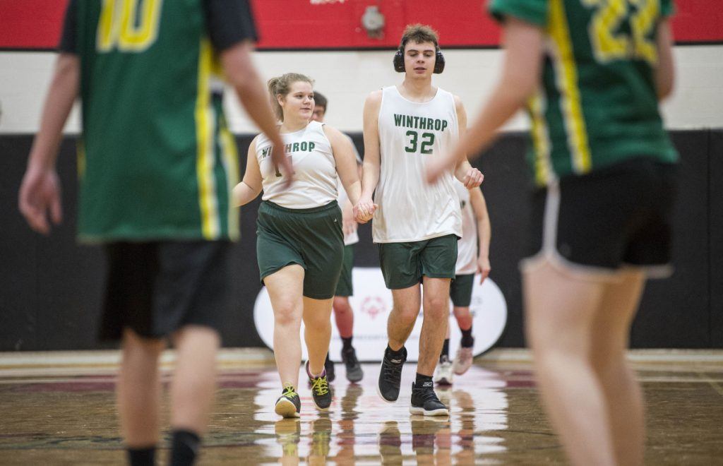 Winthrop High School's Samantha Neumann (11) holds hands with teammate Lukas Thompson (32) as they run back on defense against Massabesic at the Unified basketball tournament Saturday at Thomas College in Waterville.
