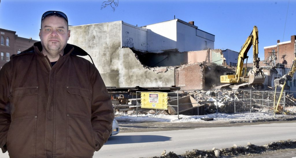 Tom Greenwood stands off Front Street in Waterville as a demolition crew tears down the former Camden National Bank on Thursday.