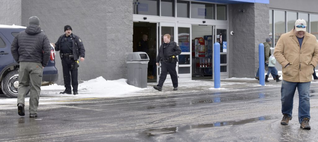Waterville police officers Steve Brame, left, and Robert Bouley exit the Waterville Walmart along with customers after police were called to the store after a man was spotted with a handgun inside the store on Monday.