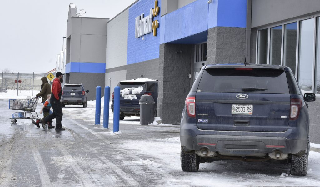 Customers at the Waterville Walmart store walk past three Waterville police cruisers while officers were inside the store investigating a report of a man with a handgun on Monday.