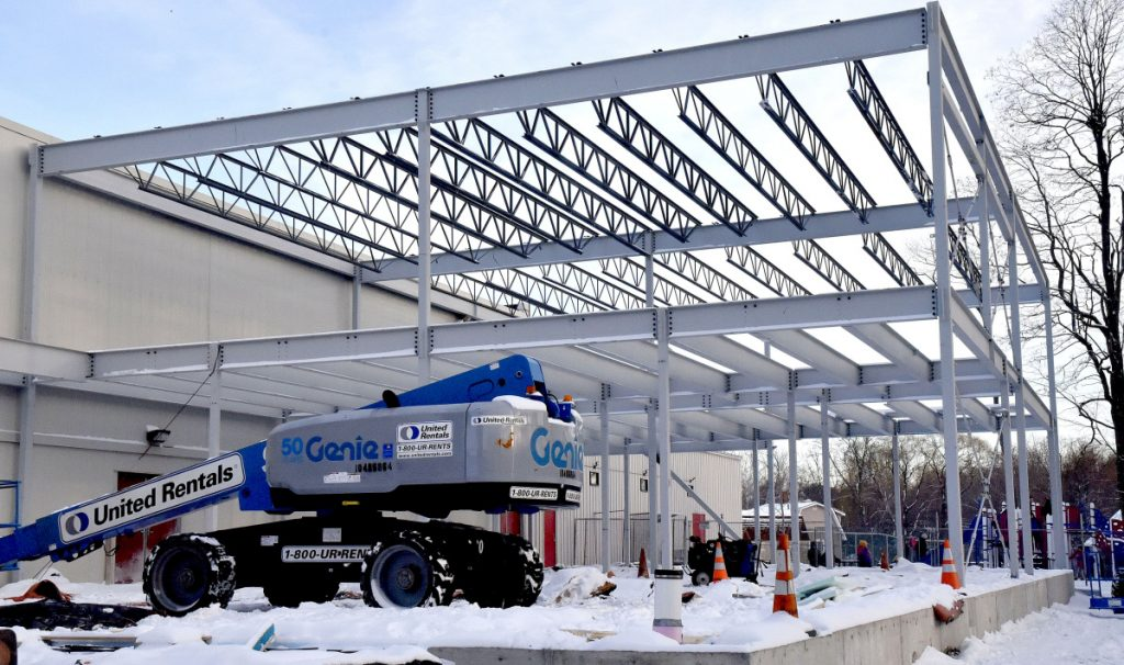As children play on an outdoor playground, background, workers erect steel girders Jan. 3 for a new Wellness Center at the Alfond Youth Center in Waterville. The center has paid the city of Waterville the full permit fee for the expansion.