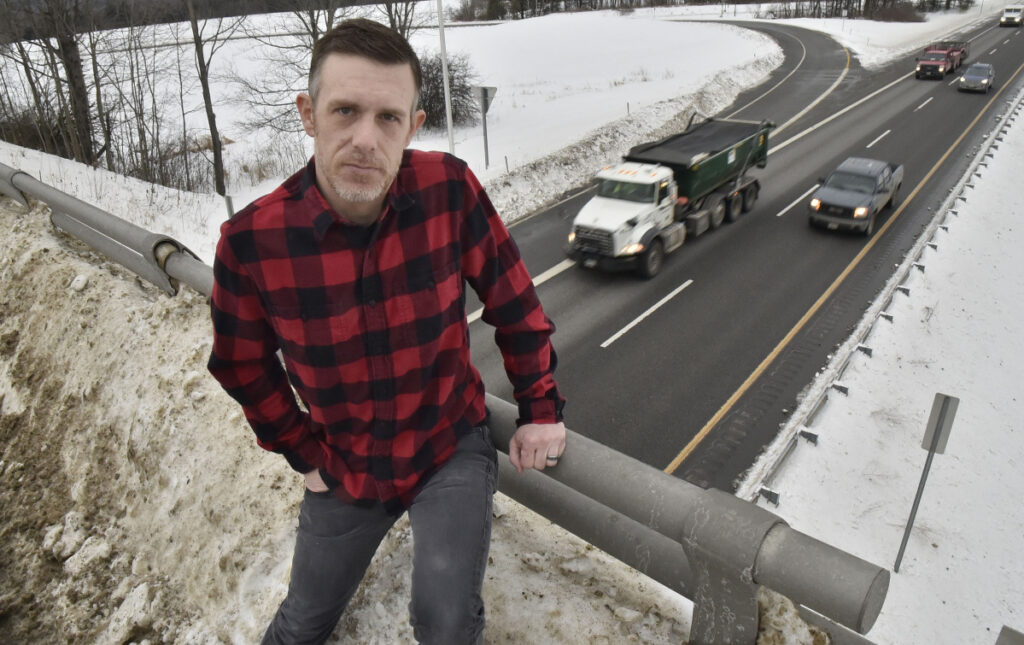 Ben Wheeler sits on a railing banked with snow Wednesday on the Trafton Road overpass on Interstate 95 in Waterville. Wheeler said a Waterville plow truck pushed heavy snow over the railing, and that the snow dropped 15 feet onto his car as he was driving north, causing an estimated $7,000 worth of damage to the front windshield and the roof.