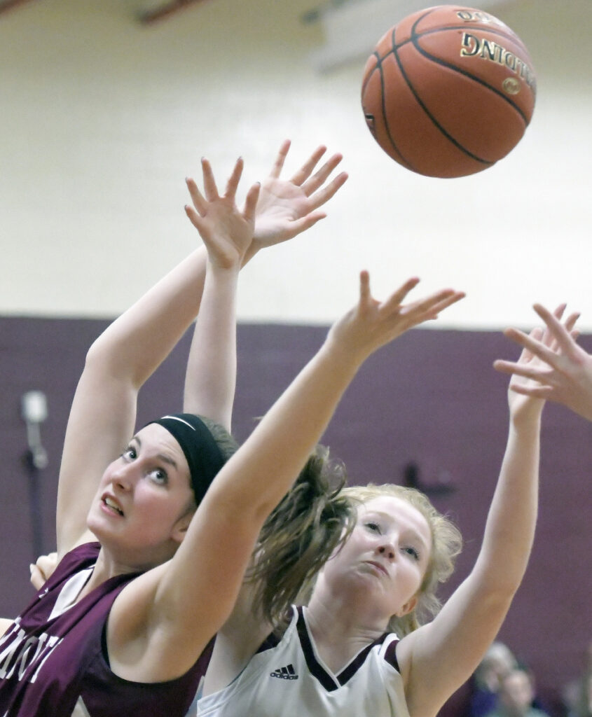 Richmond's Bryanne Lancaster, right, and Monmouth's Kaeti Butterfield reach for a rebound during a Mountain Valley Conference game Thursday in Richmond.