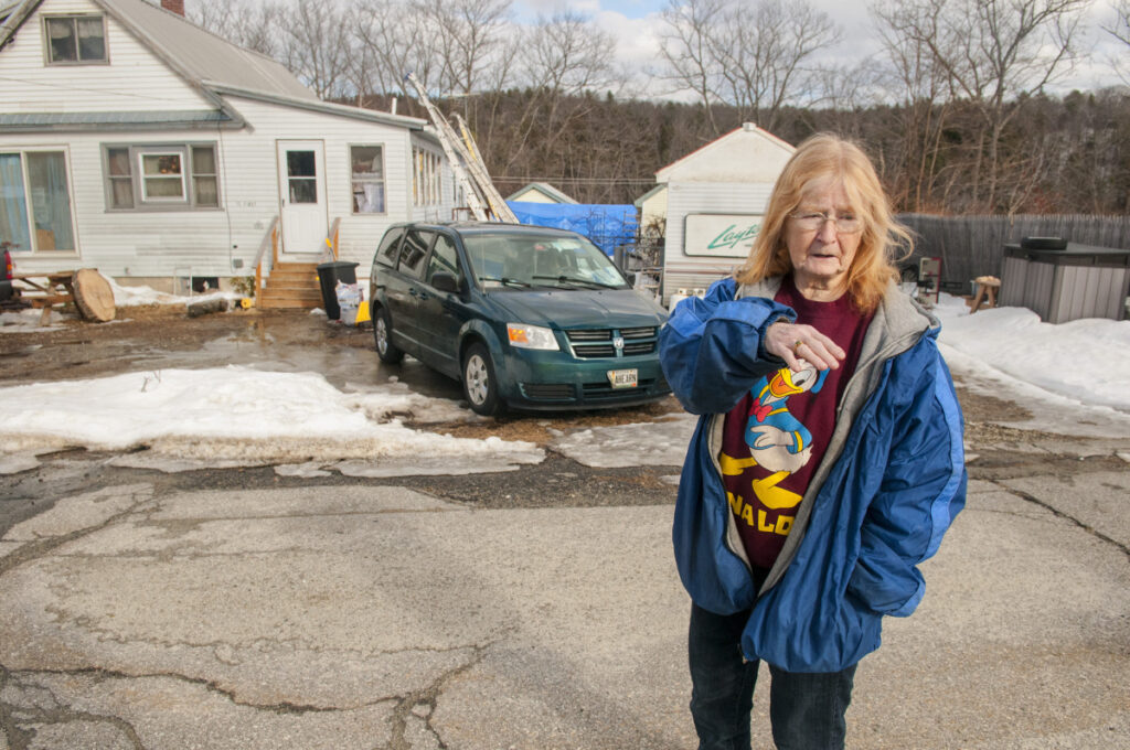 Merleen Ahearn talks about drainage problems Friday in front of her home on Clark Street Extension in Farmingdale.