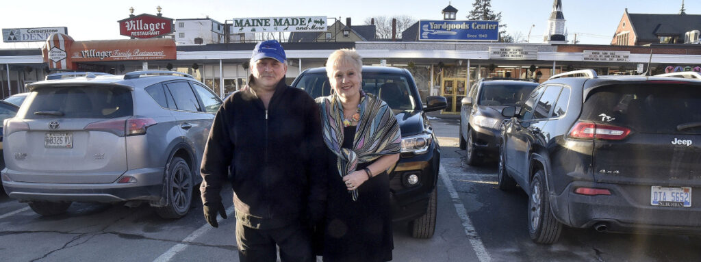 The Villager restaurant owner Joe Marcoux and Yardgoods Center owner Joyce Vlodek Atkins stand in front of their businesses in The Concourse in Waterville  on Monday. According to them, the parking lot is often filled with Colby College student vehicles, and customers have to park farther away. The City Council will consider raising parking fines and accepting a $10,000 gift from the college for parking enforcement in the two-hour lot.