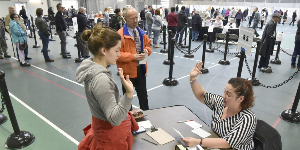 Colby College student Alexandria Fraize, left, swears the information she gave election clerk Allison Brochu is accurate before voting at Thomas College on Nov. 6, 2018. City Solicitor Bill Lee observes.
