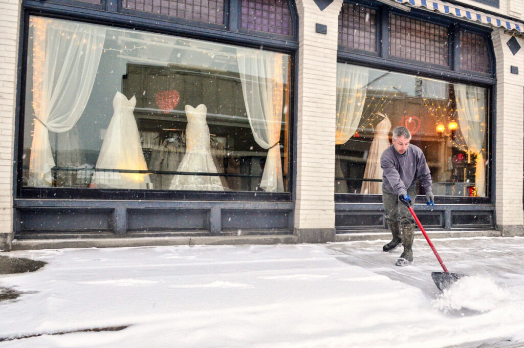 Danny Fossett pushes snow off the sidewalk around 7:30 a.m. Wednesday in front of The Dreams Bridal Boutique and Tuxedo Center on Water Street in downtown Augusta.