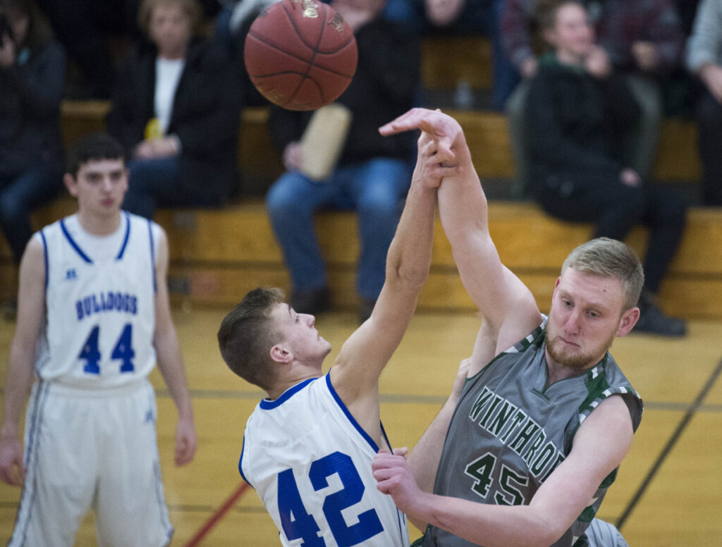 Winthrop's Cam Wood (45) wins the tip against Madison's Thomas Dean (42) to begin the game Thursday in Madison.