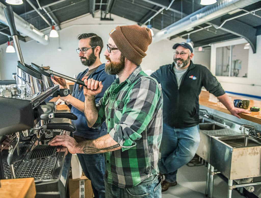 Nathan Hahn of Coffee by Design, left, walks Willis Croninger through the process of pulling the first press of espresso at Side by Each Brewing Co. in Auburn. Owner Ben Low looks on, right.