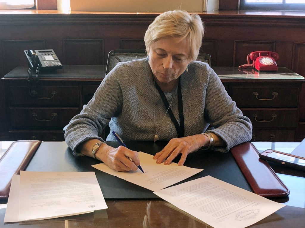 "Gov. Janet Mills signs ""Executive Order 1"" to implement Medicaid expansion on her first day in office, making more than 70,000 Mainers eligible for health insurance."