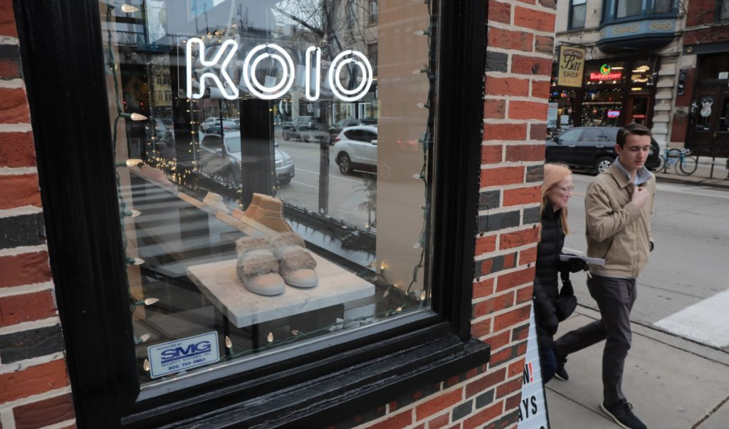 Pedestrians pass by the Koio shop, which sells Italian sneakers, on west Armitage Avenue in Chicago. Some online retailers are finding many of their customers also like a traditional shopping environment.