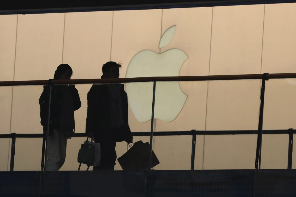 Shoppers pass by the Apple store logo Thursday at a mall in Beijing. A U.S. delegation led by a deputy U.S. trade representative, Jeffrey D. Gerrish, arrived in the Chinese capital ahead of trade talks this week.