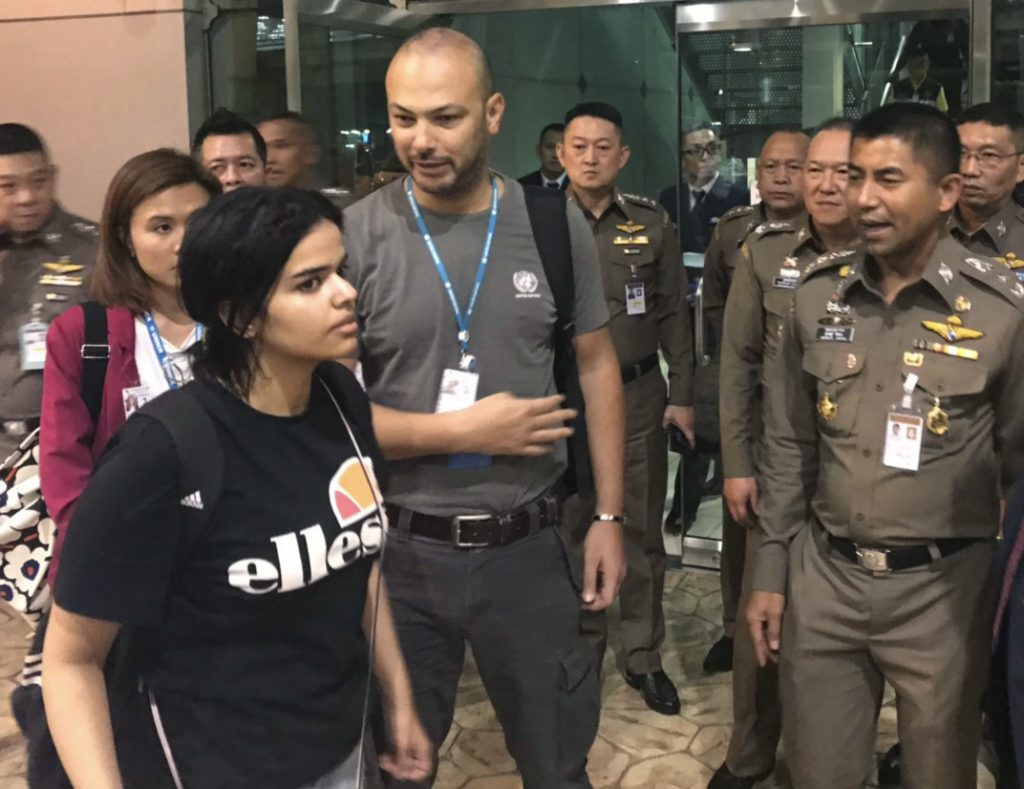 Saudi resident Rahaf Mohammed Alqunun walks past an immigration official and others Monday before leaving the Suvarnabhumi Airport in Bangkok. She had been placed in a hotel there and told she would be put on a Monday morning flight to Kuwait, but her pleas online from the room prevented that.