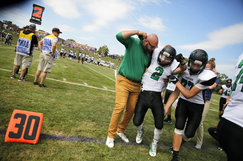 """Massabesic's assistant coach Ethan Magill and teammate Robert Woods help junior Owen Roberts off the field last season after he was hurt in a game against Cheverus in Portland. Maine does not require medical coverage in """"collision"""" sports."""