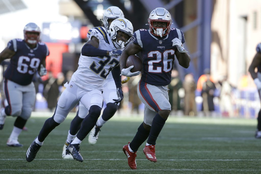 New England running back Sony Michel runs away from Los Angeles Chargers free safety Derwin James (33) during the first half of the Patriots' 41-28 win in the AFC divisional round on Sunday in Foxborough, Massachusetts. Michel rushed for 129 yards and three touchdowns to help the Patriots reach their eighth straight AFC championship game.