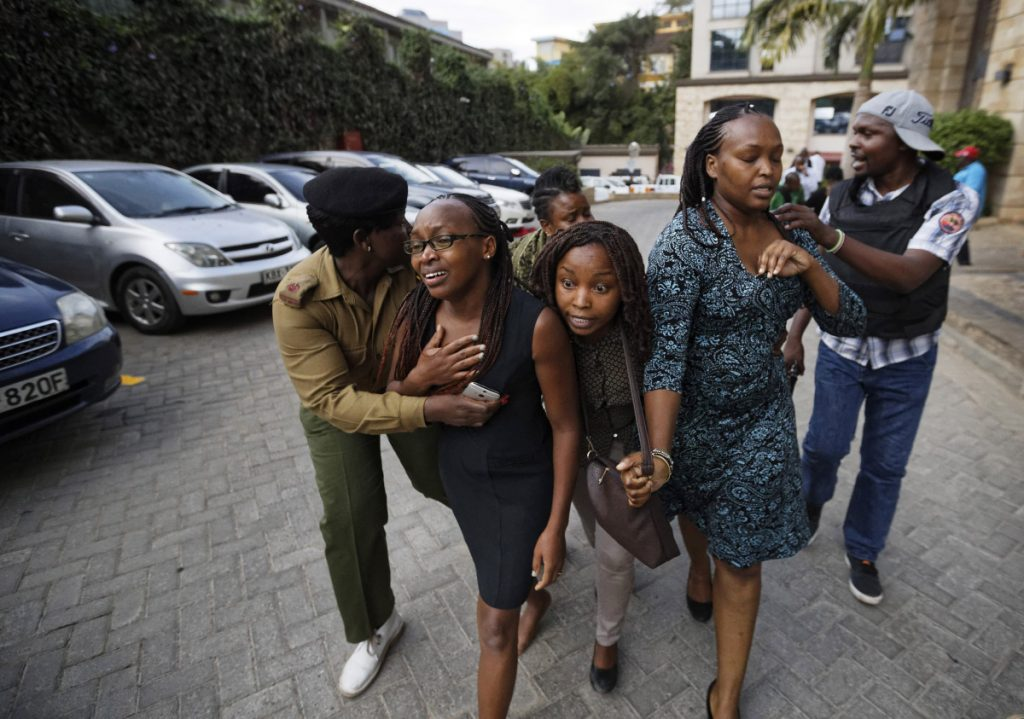 Civilians flee the scene at a hotel complex in Nairobi, Kenya, on Tuesday. An upscale hotel complex in Kenya's capital came under attack on Tuesday, with a blast and heavy gunfire. The al-Shabab extremist group based in neighboring Somalia claimed responsibility and said its members were still fighting inside.