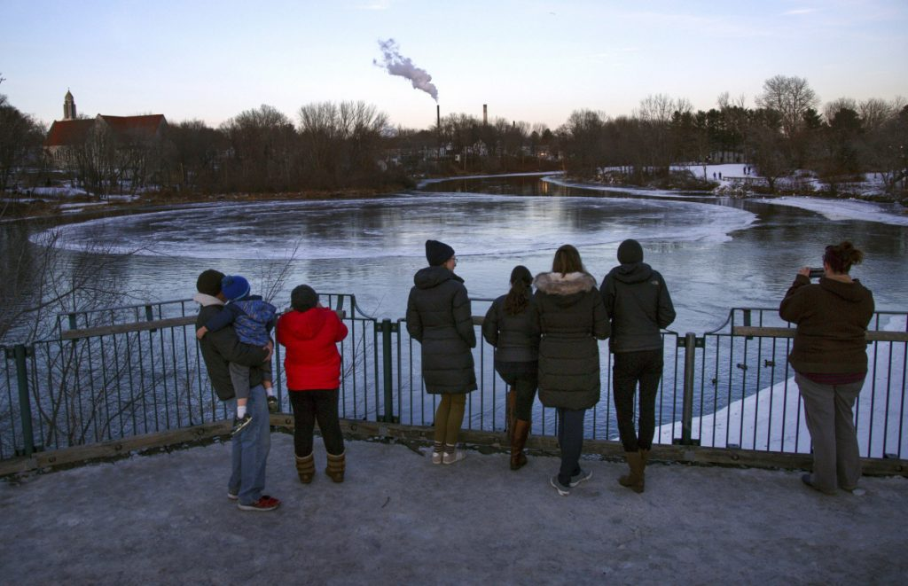 "People gather to watch the ice disk on Jan. 17. The natural phenomenon has been a boon for businesses in Westbrook, where one bar has named a cocktail the ""Ice Disk Cosmo."""