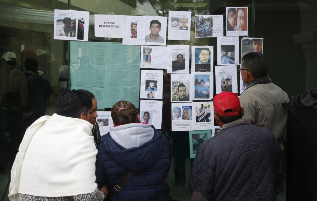 People look at photographs of people who are missing since the pipeline accident in Tlahuelilpan, Mexico, Sunday. At least 79 people were killed in the explosion.