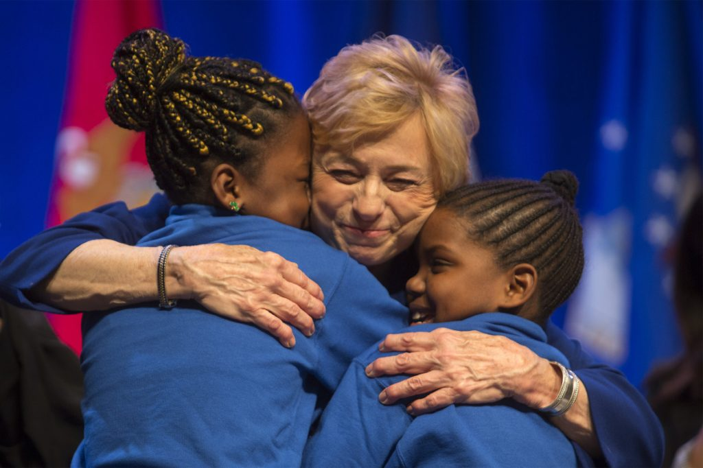 """Gov. Janet Mills hugs Natalia Mbadu, 10, and Shy Paca, 11, after they sang a rendition of the song """"Girl on Fire"""" during her inauguration ceremony at the Augusta Civic Center on Jan. 2."""