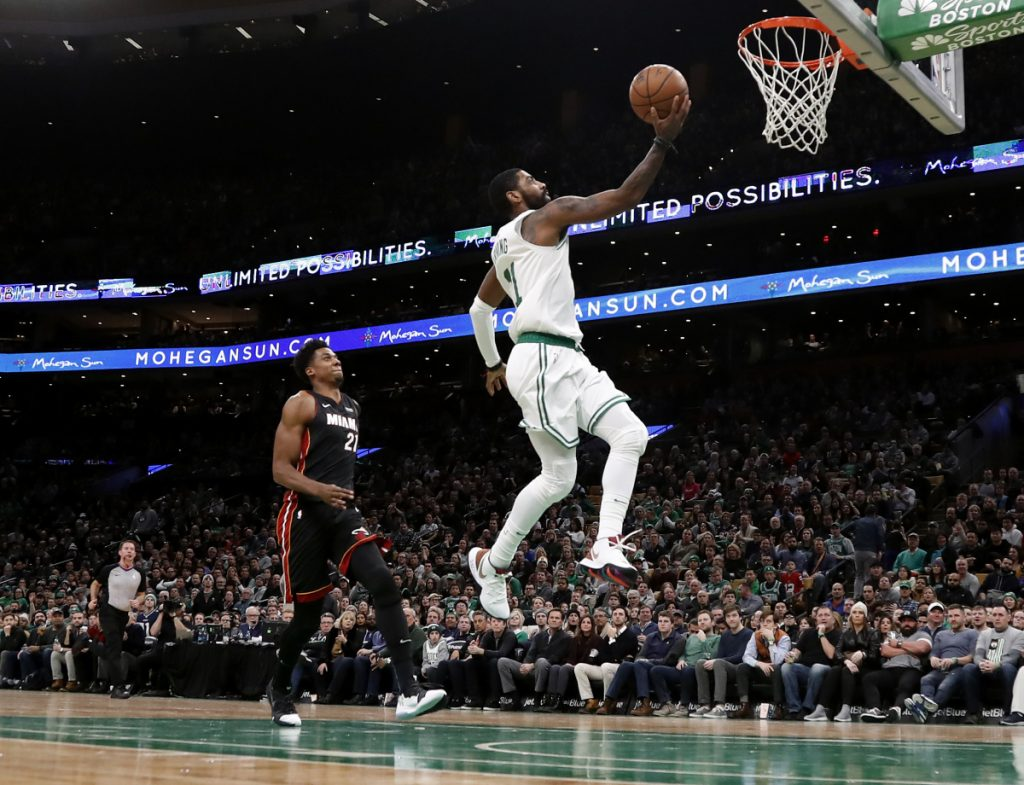 Boston's Kyrie Irving, right, goes in for a layup past Miami's Hassan Whiteside during the second quarter of the Celtics 107-99 win Monday in Boston.
