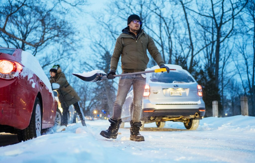 Joshua Locke of Portland shovels out his wife's vehicle from the parking area in Deering Oaks on Monday morning.