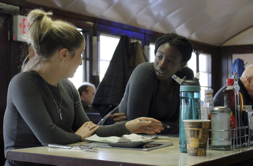 Waitress Kelcie Tipping, left, speaks with fellow waitress Mariam Touray Friday at the Modern Diner in Pawtucket, R.I. Tipping believes the economy is doing well, while Touray said the country is not in a good place.