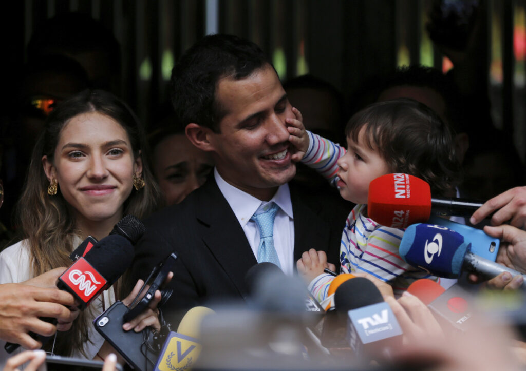 Opposition National Assembly President Juan Guaido, accompanied by his wife, Fabiana Rosales, smiles at his 20-month-old daughter, Miranda, during a news conference outside their apartment, in Caracas, Venezuela, Thursday. Guaido said security forces showed up at their home in an attempt to intimidate him. (AP Photo/Fernando Llano)