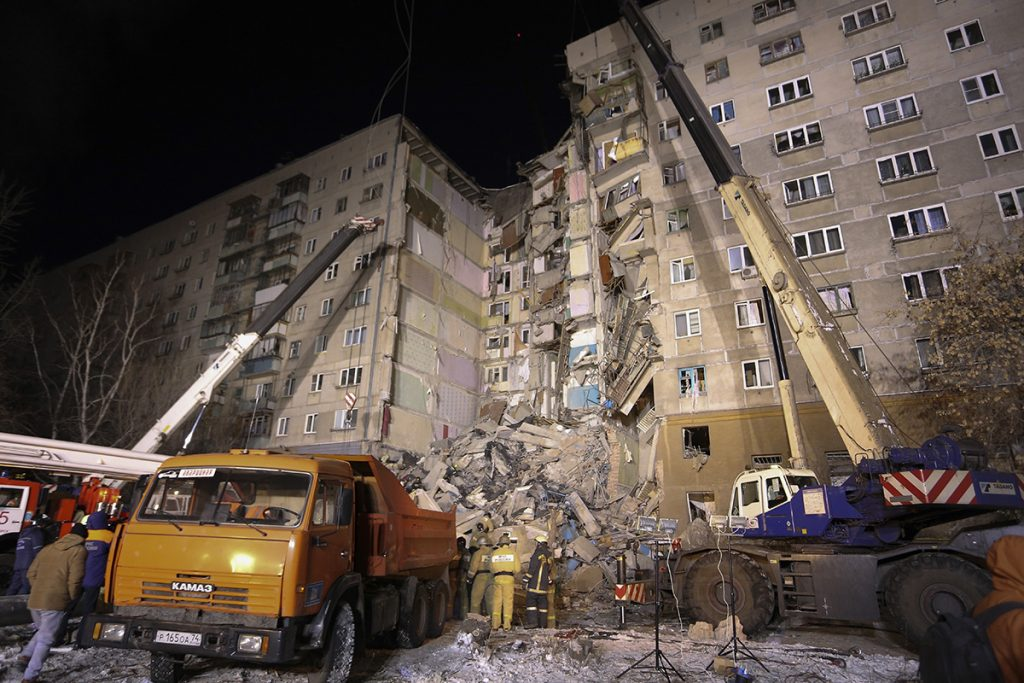 Emergency Situations employees working at the scene of a collapsed apartment building in Magnitogorsk, a city of 400,000 people, about 1,400 kilometers (870 miles) southeast of Moscow, Russia, Monday, Dec. 31, 2018. At least four people died Monday when part of a 10-story apartment building collapsed in Russia's Ural Mountains region, and hundreds of rescuers searched for survivors under the rubble in the frigid weather.