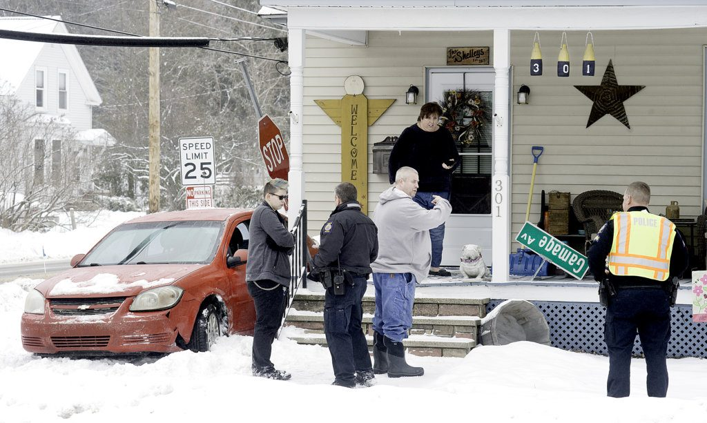 The homeowners talk with Auburn Police Sgt. Chad Syphers, right, after a car slid into the side of the house at 301 Gamage Ave. in Auburn on Tuesday. Minimal damage was done to the front porch, according to Auburn firefighters on scene.