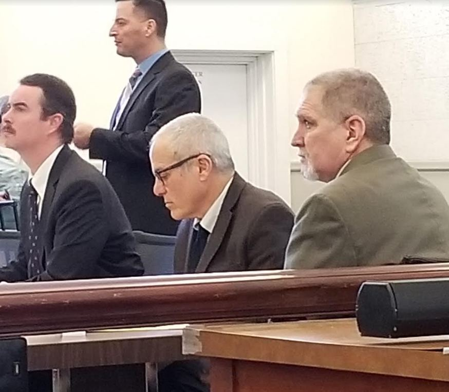 James Sweeney, 58, formerly of Jay, listens to closing arguments Monday during his murder trial in Franklin County Superior Court. His lawyers, seated from left, are Thomas J. Carey and Walter Hanstein. Standing behind them is Detective Michael Chavez of the Maine State Police.