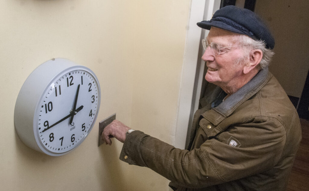 Jim Bryant waits until a pilot clock reaches 12:45 p.m. to flip a switch to turn on the tower clock Thursday at the Cony Flatiron Senior Residence in Augusta.