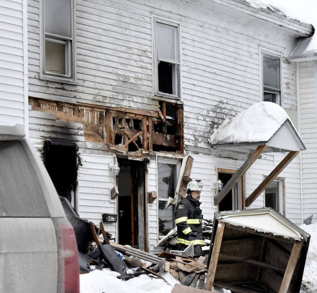 Skowhegan Fire Chief Shawn Howard exits through a fire-damaged entryway Sunday at an apartment house at 386 Water St. in Skowhegan after fire broke out there that morning.