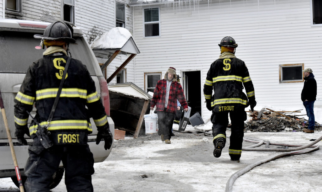 At center, a man carries items past Skowhegan firefighters from the home at 386 Water St. in Skowhegan after fire broke out there Sunday.