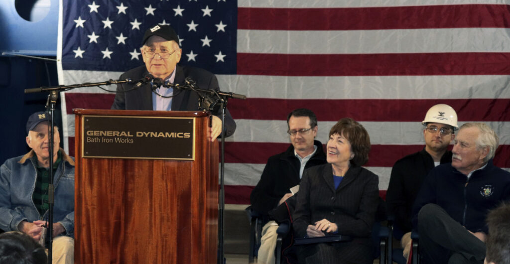 Retired U.S. Sen. Carl Levin of Michigan addresses a gathering Friday at Bath Iron Works in Bath. Seated in the front row are: Navy Secretary Richard Spencer, from left, and U.S. Sens. Susan Collins and Angus King, both of Maine.
