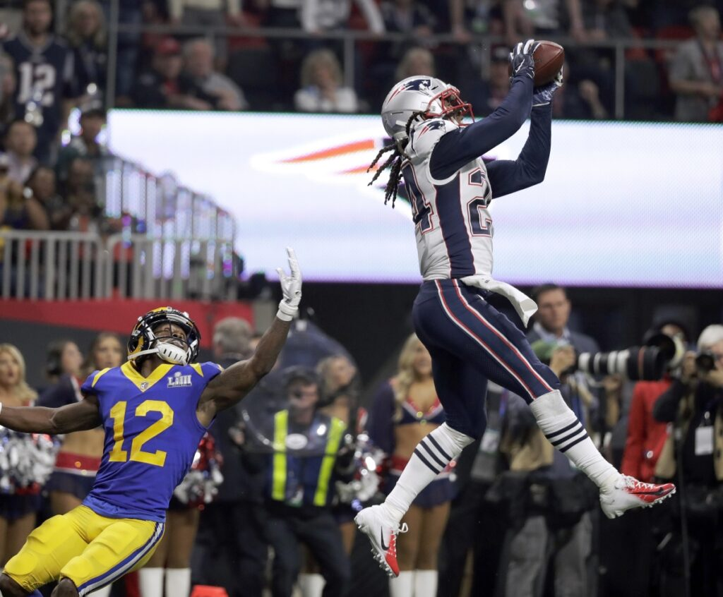 Patriots cornerback Stephon Gilmore intercepts a pass intended for Brandin Cooks of the Rams in the fourth quarter of the Super Bowl. The interception highlighted an outstanding defensive performance by the Patriots in a 13-3 victory.