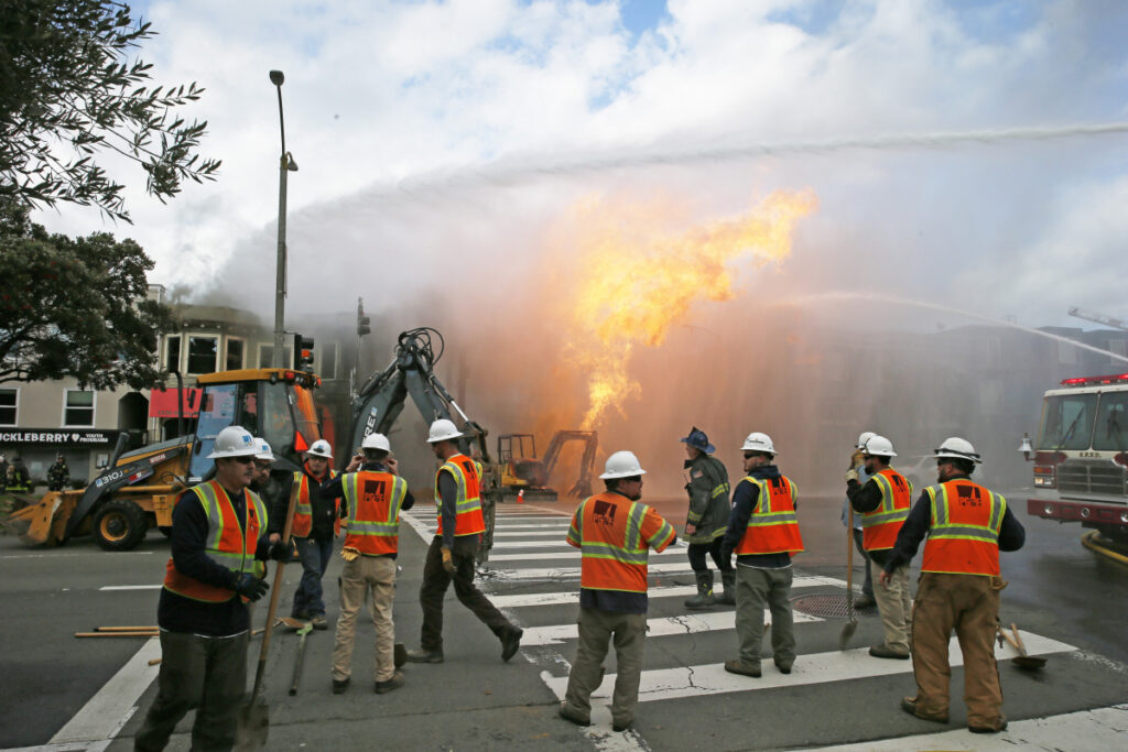 PG&E officials stand by as firefighters battle a fire following a gas explosion Wednesday in San Francisco, Calif. Utility crews scrambled to shut off the flow of gas more than two hours after the blaze began. Private construction workers cut a natural gas line, San Francisco Fire Chief Joanne Hayes-White said.