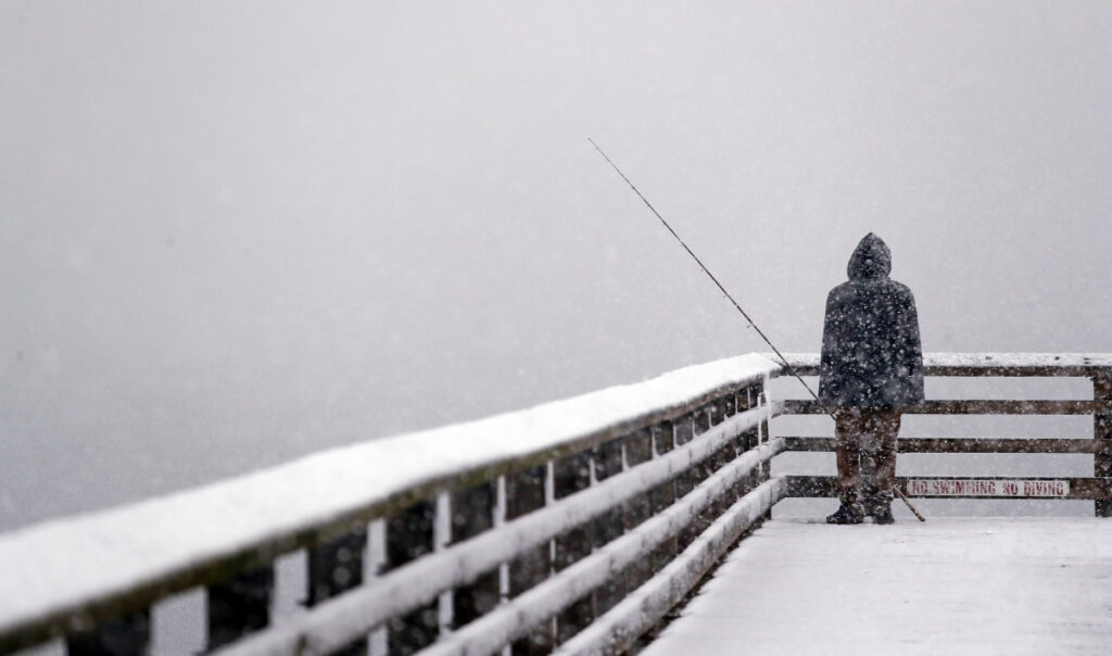 Hershel Odle looks out toward the cityscape lost in a whiteout as he fishes from a pier during a snowstorm Friday in Seattle. More than a foot of snow was recorded in some areas, including on the Olympic Peninsula.