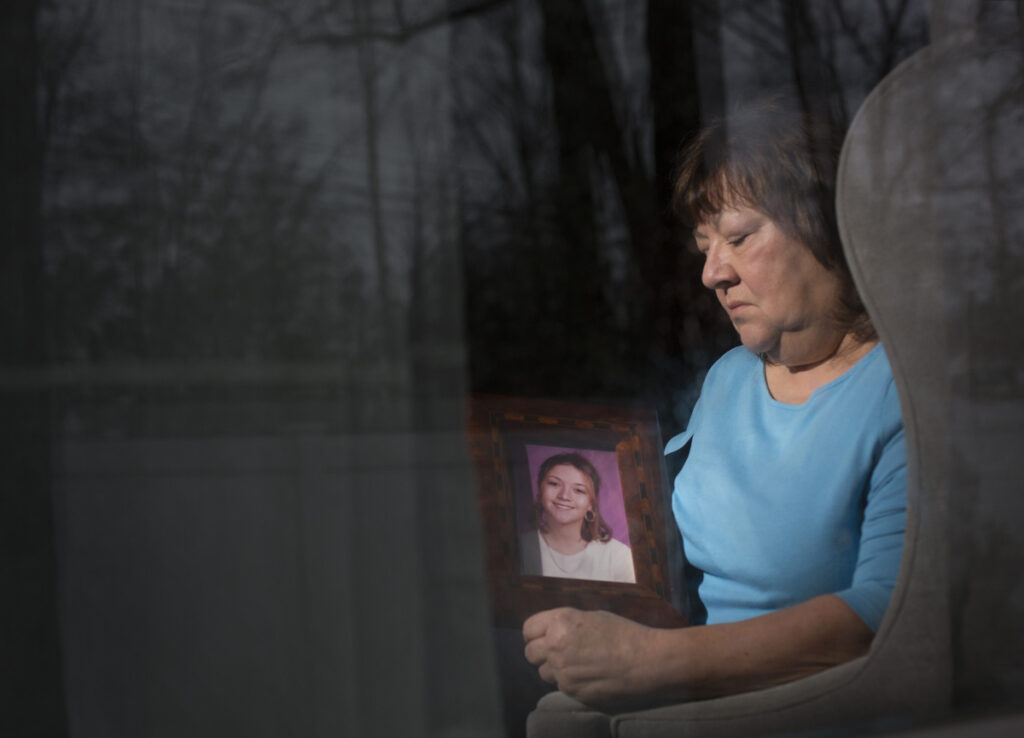 """Lise Ouellette of Old Orchard Beach holds a portrait of her daughter Ashley, who was killed 20 years ago in a case that remains unsolved. """"There's no time limit on grieving,"""" says the anguished mother, who still hopes for resolution. """"I just want to know why."""""""