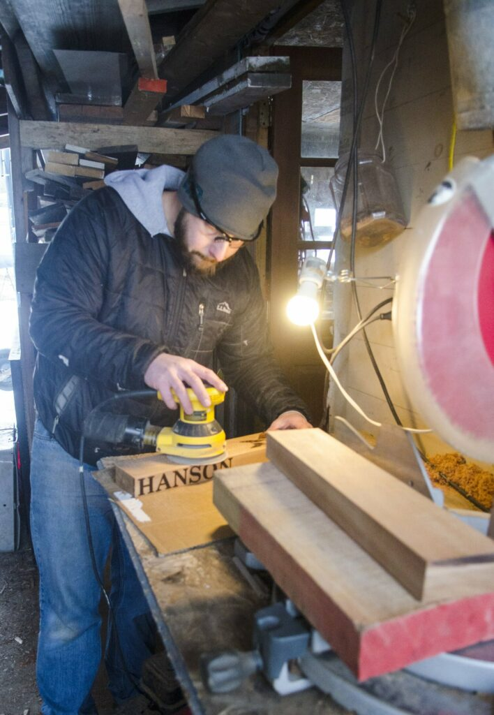 In his unheated woodshed, William Terry sands a cribbage board after drilling its holes Feb. 2 in Richmond.