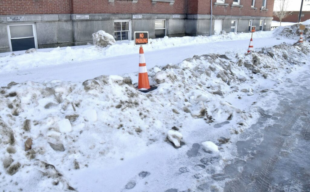 Snow slid off the roof of the Court House in Skowhegan, and was blocking parking spots Tuesday for commissioners, administrators and jail transport vehicles.