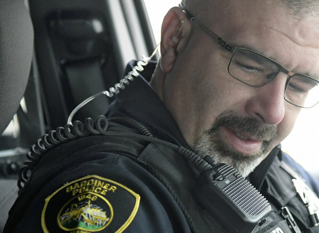 Gardiner police Officer Marcus Niedner wears an earpiece and microphone to respond to radio calls on Feb. 7.