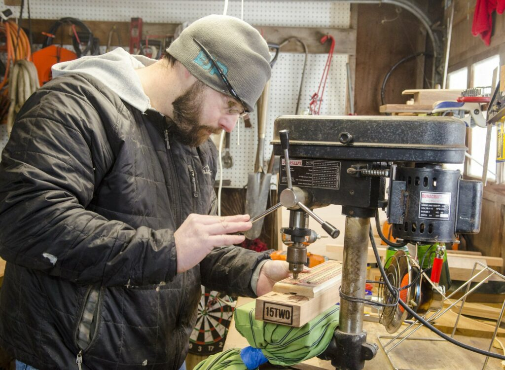 William Terry uses a drill press to drill holes into a cribbage board that he's making Feb. 2 in Richmond. He uses an old cribbage board as a guide.