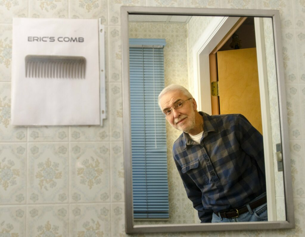 Eric Anderson poses for a portrait on Tuesday at the Farmingdale town office. The comb was hung up by town office staffers as a joke for Anderson who, until he recently retired, was U.S. Postal Service letter carrier for the office.