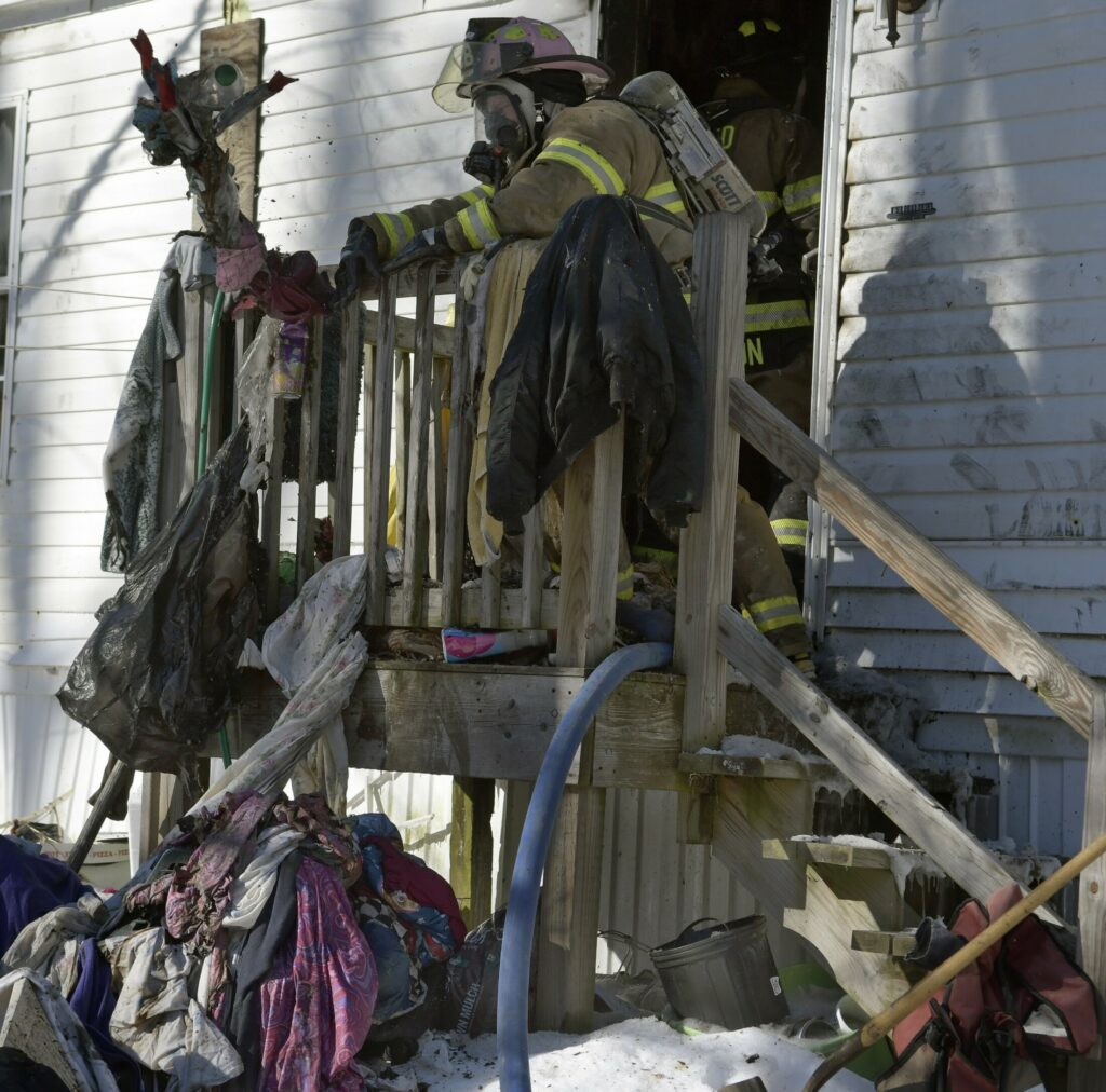 A firefighter tosses items that burned Monday during a fire at a residence in Mt. Vernon.