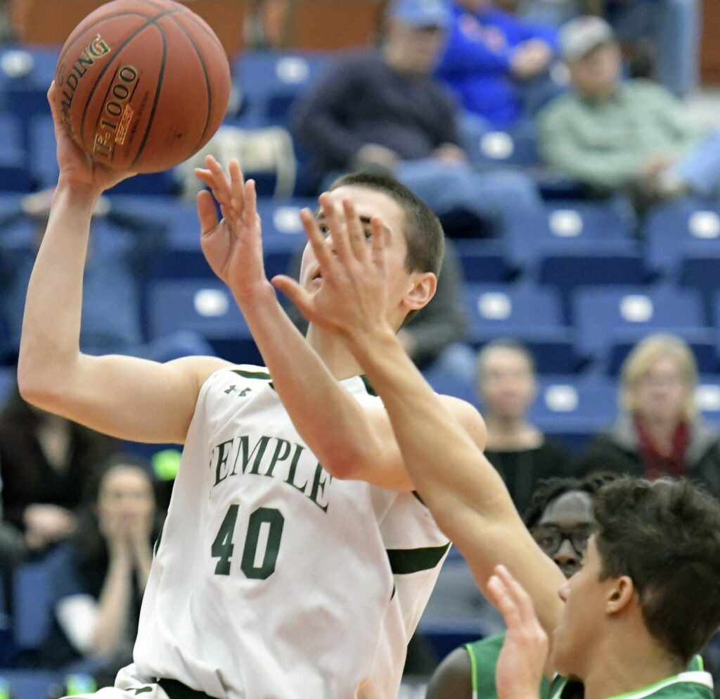 Temple Academy junior Stevo Kruta goes up for a shot as Pine Tree Academy's Jobet Tardiff defends during a Class D South quarterfinal game Monday at the Augusta Civic Center.